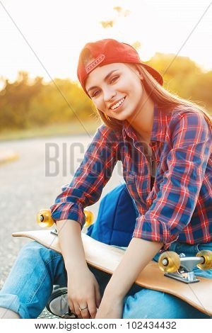 Beautiful Smiling Girl With A Skateboard On The Background Of Sunset.