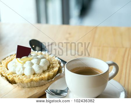 Warm Tone Of A Cup Of Espresso Coffee And Blurry Cake On Wooden Brown Table.