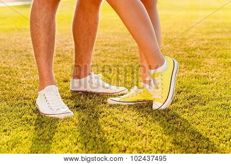 Man's And Woman's Legs.  Couple In Love On The Lawn