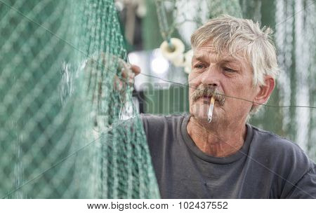 Deckhand on commercial fishing vessel mending nets