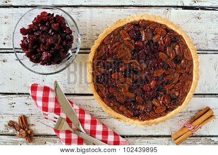 Pecan and cranberry pie table scene on rustic white wood