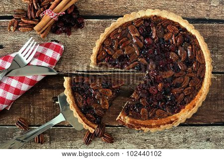Pecan and cranberry pie, rustic table scene with slice removed