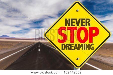 Never Stop Dreaming sign on desert road