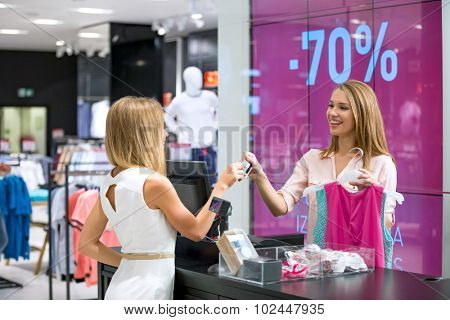 Young girl at the checkout makes shopping