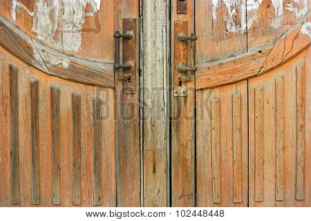 Low part of a brown wood weathered door with two rusty handles