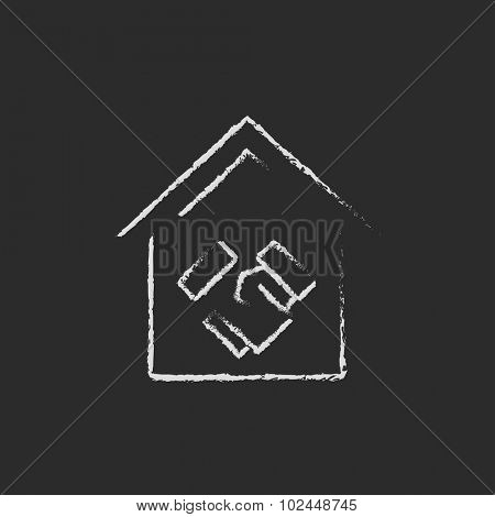 Handshake and successful real estate transaction hand drawn in chalk on a blackboard vector white icon isolated on a black background.