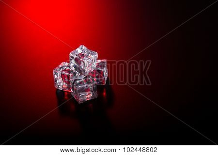 Ice cubes on black background with red club style light