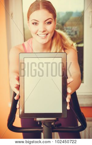 Woman On Exercise Bike Holding Pc Tablet Copyspace