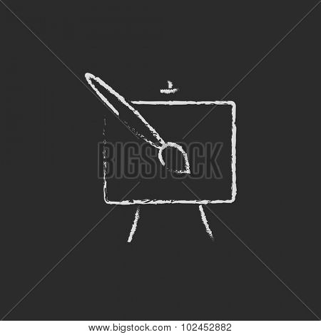 Easel and paint brush hand drawn in chalk on a blackboard vector white icon isolated on a black background.