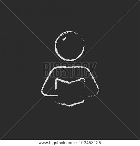 Man reading a book hand drawn in chalk on a blackboard vector white icon isolated on a black background.