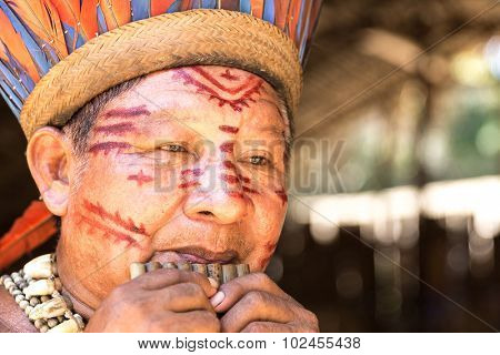 Native Brazilian man playing wooden flute at an indigenous tribe in the Amazon