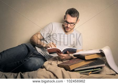 Student reading a book while lying on his bed