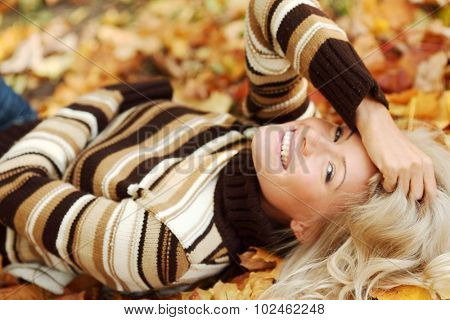 Beautiful dreamy woman laying down on dry autumn leaves