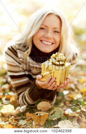 Woman with gift laying on dry autumn leaves