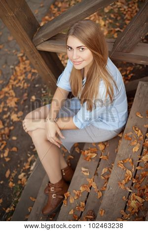 girl sitting on the steps of the wooden porch, autumn season