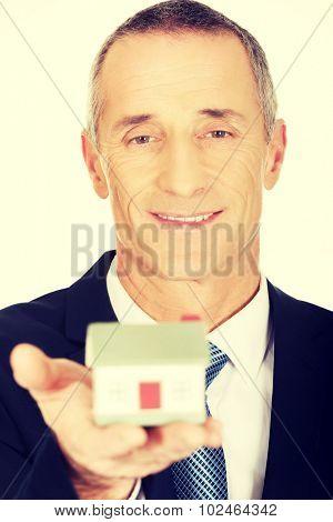 Mature businessman holding house model.