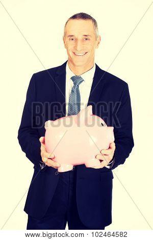 Cheerful mature businessman holding piggybank.