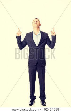 Handsome smiling businessman pointing upwards.