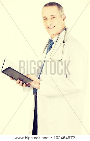 Experienced mature male doctor holding notebook.