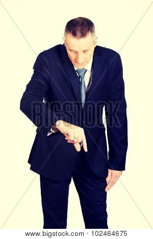 Mature businessman showing small size with fingers.