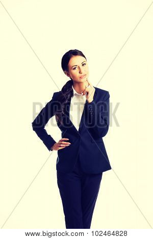 Thoughtful businesswoman with a finger under chin looking at the camera.