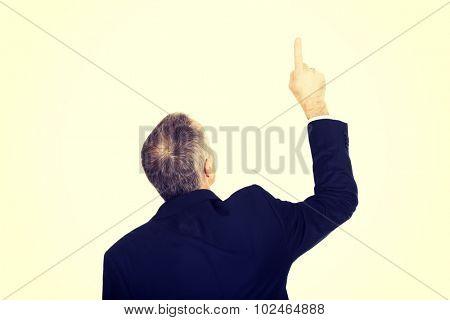 Back view businessman pointing upwards.