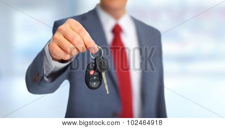 Hand with a new Car keys over garage background.