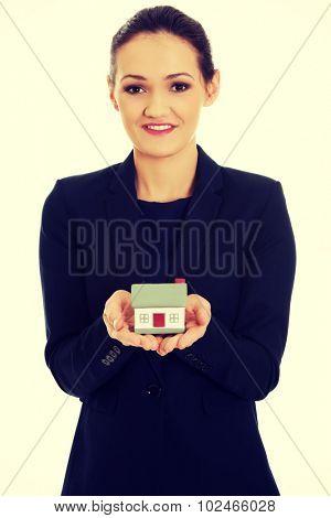 Female business agent holding house model.