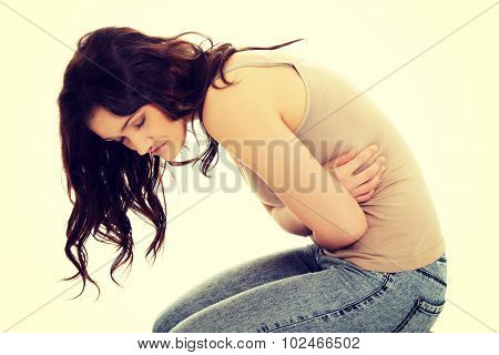 Young student woman curled up with a huge stomachache.
