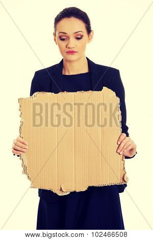Fired businesswoman with piece of cardboard.