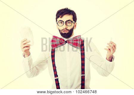 Surprised man wearing suspenders with menstruation pad.