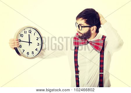 Worried man wearing suspenders holding big clock.