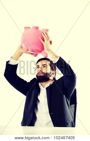 Young businessman searching money in piggybank.
