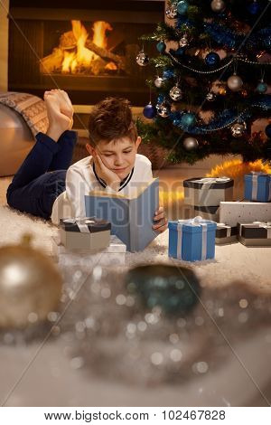 Young boy lying on front by christmas tree, reading book surrounded by christmas presents.
