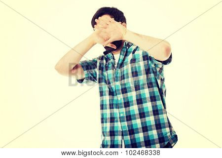 Young handsome afraid man covering his face.