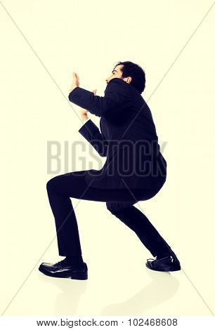 Businessman trying to protect himself from unpleasant situation.