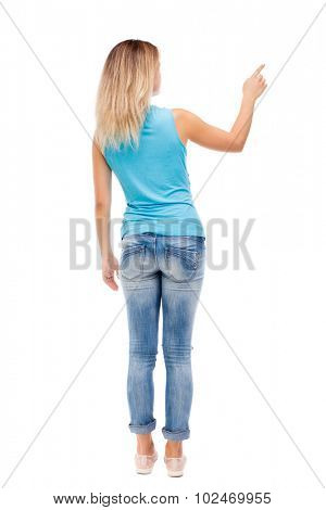 Back view pointing woman. beautiful girl. Rear view people collection.  backside view of person.  Isolated over white background. The girl in jeans and a blue shirt shows a finger of his right hand.