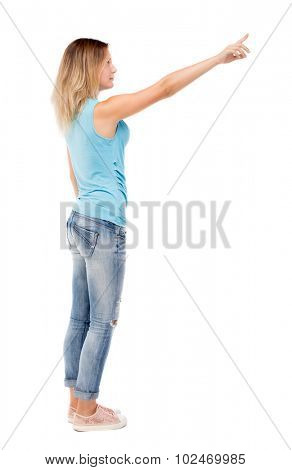 Back view pointing woman. beautiful girl. Rear view people collection.  backside view person. Isolated over white background. The girl in jeans and a blue t-shirt standing sideways and shows a hand up