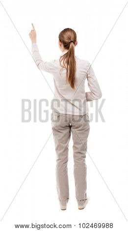Back view pointing woman. beautiful girl. Rear view people collection.  backside view person.  Isolated over white background. A girl standing in a light denim suit and shows up with his left hand.