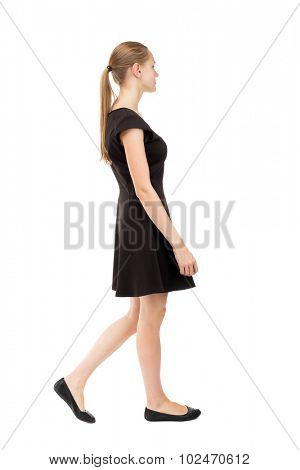 back view walking woman in dress. beautiful blonde girl in motion.  backside view of person. Rear view people collection. Isolated over white background. The blonde in black short dress goes to right