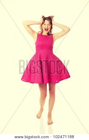 Frustrated teenage woman with pink skirt