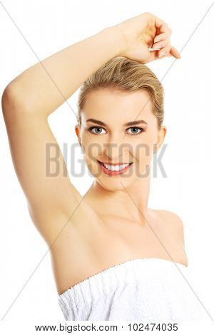 Beautiful happy spa woman showing her shaved armpit.