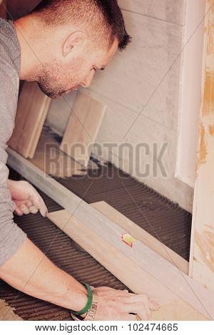 Tiler installs ceramic tiles at home.