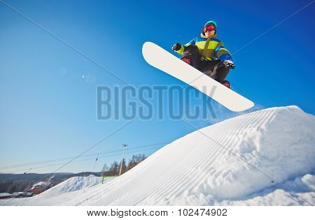 Active young man on snowboard hanging over snowdrift