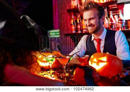Happy barman welcoming guests on Halloween party