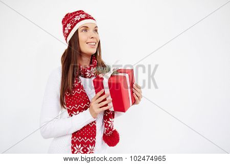 Pretty young female in cap, sweater and scarf holding giftbox