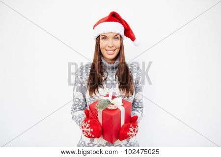 Pretty girl in sweater, Santa cap and mittens holding giftbox