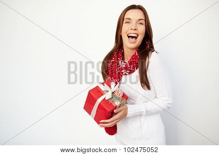 Ecstatic girl with Christmas gift looking at camera