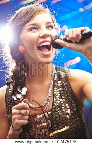 Ecstatic young woman singing karaoke