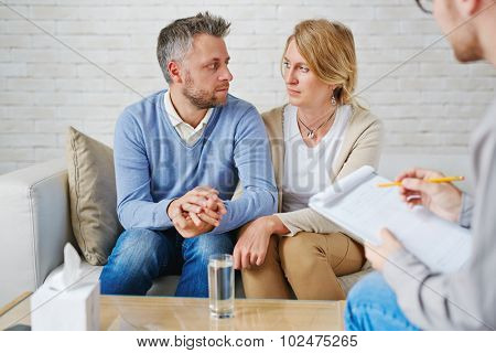 Sad couple sitting on sofa in front of psychologist
